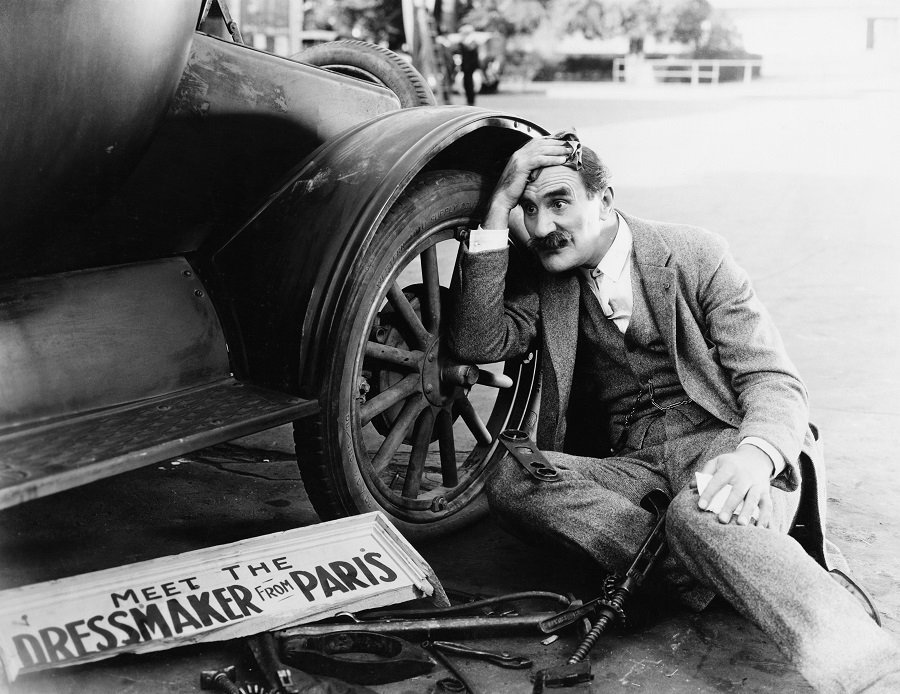 Black and White Image of Man with Old Car
